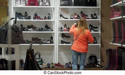 Woman back in a shoe store, chooses his boots and shoes.