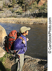 woman backpacker by river