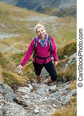Woman backpacker hiking on a trail