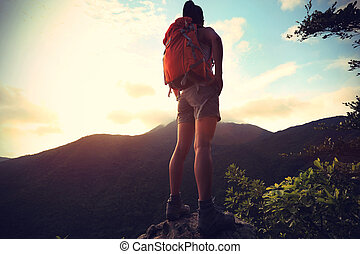 woman backpacker on mountain peak enjoy the view