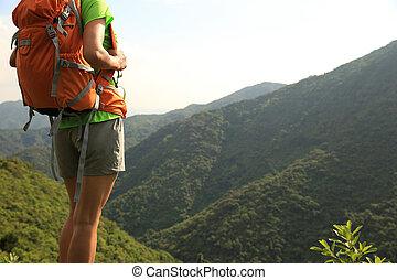 woman backpacker on mountain peak