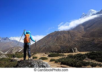 Woman backpacker trekking at the himalaya mountains