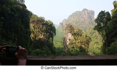 woman backside view takes pictures of canyon cliffs in jungle