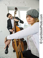 Woman backwards on chair and contrabas player