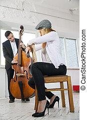 Woman backwards on chair listen contrabass play