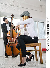 Woman backwards on chair listen contrabass play