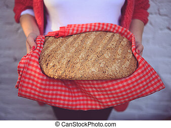 Woman baker holding freshly baked bread - Home meade bun of bread
