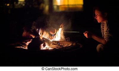 Woman bakes apple on bonfire