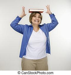 Woman balancing book.