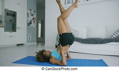 Woman balancing on mat training yoga - Shaped young model in...