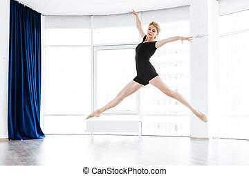 Woman ballerina dancing and jumping in ballet studio