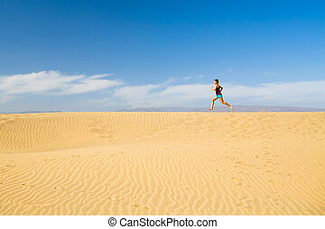 Woman barefoot running on sand desert dunes