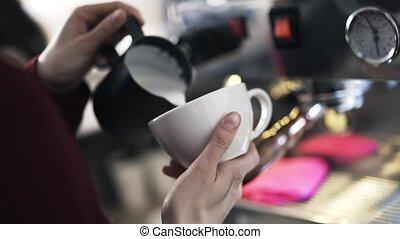 Woman barista adding milk to coffee