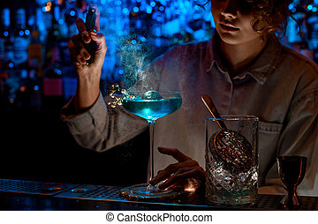 Woman bartender carefully sprinkles on glass with blue cocktail