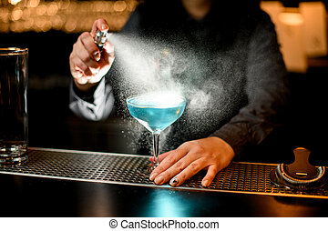 woman bartender spraying on glass with blue cocktail.