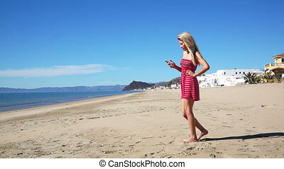 Girl on a beach at Bahia Kino, Sonora, Mexico wearing a dark pink sundress and taking a selfie picture of herself with her phone dolly shot.