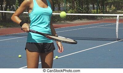 Woman beating ball by tennis racket