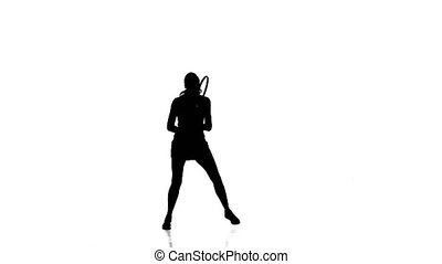 Sportswoman of the racket hits the ball while jumping sideways. White background. Silhouette