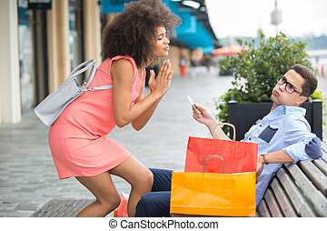 Woman begging partner for credit card while out shopping