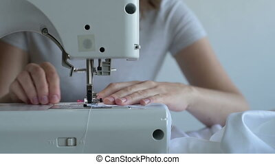 Woman begins sewing a sheet - Close up of a woman sewing a...