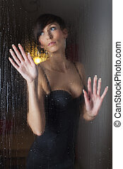 woman behind a rainy window