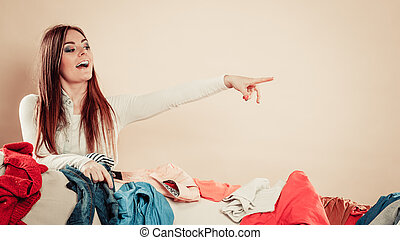 Woman behind sofa full of clothes point with finger. - ...