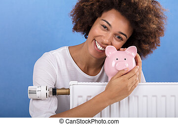 Woman Behind The Heating Radiator Holding Piggy Bank