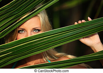 woman behind the palm leaves - woman hiding behind the palm...