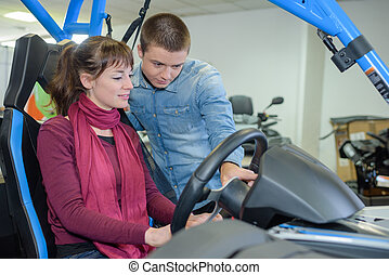Woman behind wheel of vehicle with roll bar