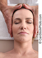 Woman being given a head massage.