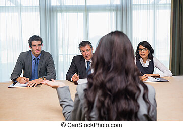 Woman being interviewed for new job by panel of business...