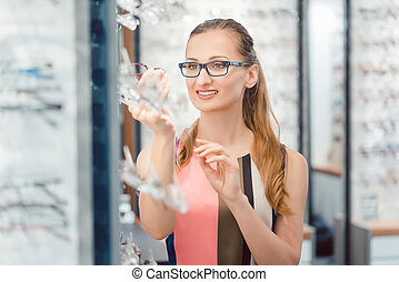 Woman being satisfied with the new eyeglasses she bought in the store