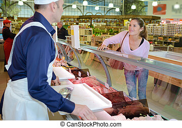 Woman being served by butcher