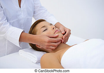 Woman being treated to face massage