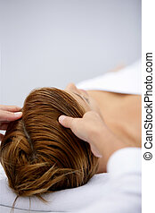 Woman being treated to soothing head massage