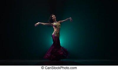 Woman belly dancer arabian in exotic dress dancing. Smoke...