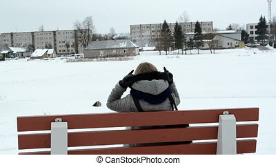 woman bench winter house - woman with coat put head hood sit...