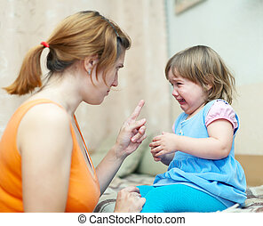Woman berates crying baby at home interior. Focus on child only