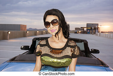 Woman beside convertible luxury car