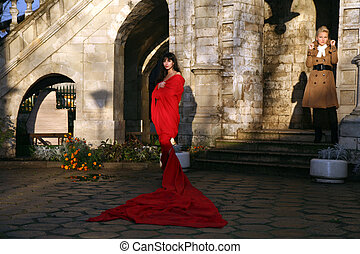 woman beside old castle in red fabr