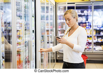 woman, bewegliches telephon hält, an, lebensmittelgeschäft