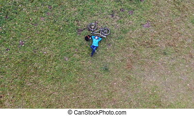 Woman bicycle rider relaxing having rest on green lawn, ...