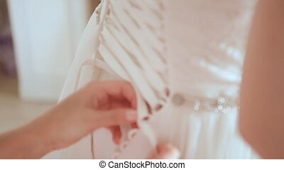 Woman binding up wedding dress