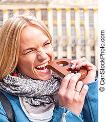 Woman bites a bar of chocolate at the Grand Place in Brussels, Belgium