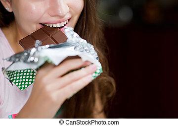 woman bites a chocolate bar. Close-up
