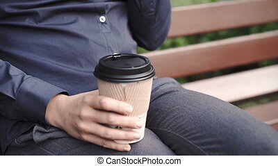Woman bites donut and drinking coffee