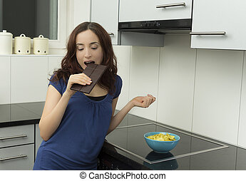 Woman biting chocolate in the kitchen
