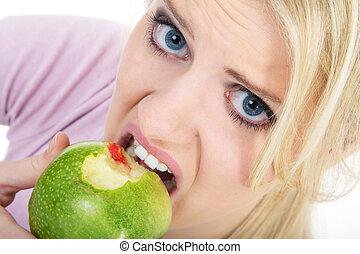 woman biting into apple, gum bleeding