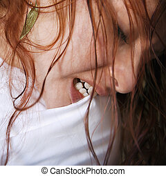Close up of pretty young redhead woman biting pillow.
