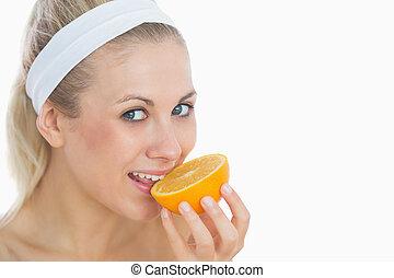 Woman biting slice of orange